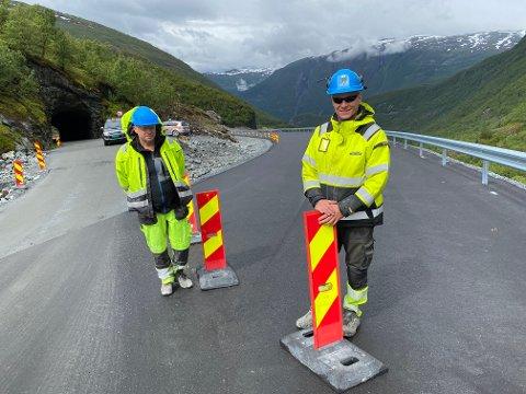 OPNING: Formann Geir Helland og anleggsleiar Egil Ørnes, fjerna sperrestolpane og markerte dermed opning av ny parsell forbi Holsbrutunnelen (t.v.), tre månader før tida.