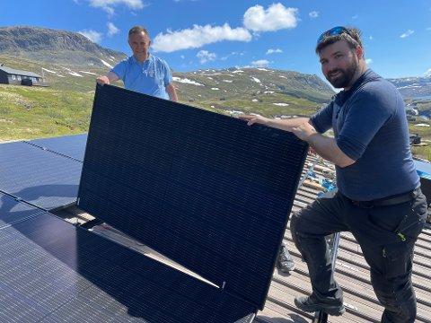 SOLCELLEPANEL: Her legg Olav Kjell Moen, hytteeigar, og Fredrik Bjørk, konstituert leiar i det lokale selskapet Solisi/Bluetec Vest, solcellepanel på hyttetaket på Mannsbergi i Årdal kommune.