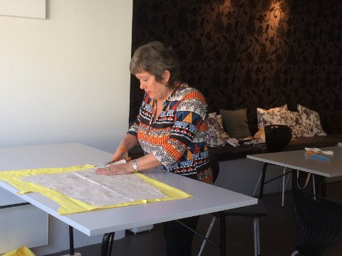 DUGNAD: Esther Tungland i Jørpeland Sanitetsforening klippar i tøyet som skal bli til ein smittevernfrakk.