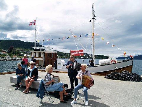 GOD STEMNING: Trioen frå Strand Toraderlag og veteranbåten Lyngøy var med og sette stemninga blant folk i Hjelmelandsvågen.