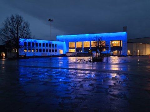 """Det nyoppussede samfunnshuset - her med blå lyssetting - rommer aktivitet for folk i alle aldre, blant annet kulturskolen. Tirsdag og onsdag har de """"åpent hus""""."""