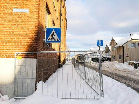 Det er trangt på fortauet utenfor Bratsbergkleiva skole. Kommunen har satt opp sperring for å hindre folk i å få istapper i hodet.