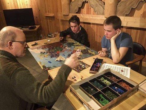 Brettspillkveld: Sigurd Haug (f.v.), Patrick Karlsen og Magnus Haug rundt et av brettspillene en tidligere spillekveld på Kafé Olea. Førstkommende fredag er det bare å møte opp og bli med, og da blir det også nattkafé. (privat foto)