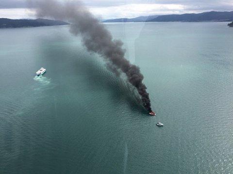 Bilete av båten i brann. Foto av luftambulansen.