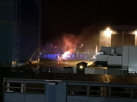 Brannvesenet i full gang med slukking av brann i en konteiner.