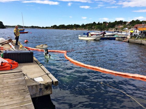 LEKKASJE: Det lekker olje og diesel fra skøyta som har sunket. Brannvesenet la tirsdag ut lenser for å begrense spredningen i sjøen.
