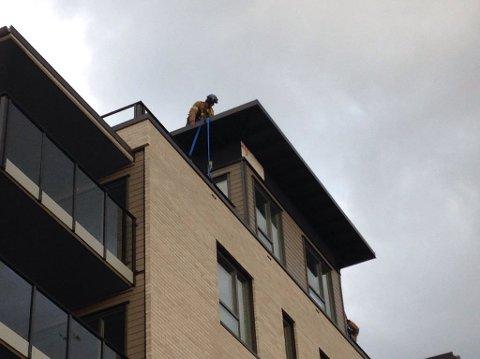 Her sikrer en brannmann takplatene fra å blåse ned på det høye bygget på Torstrand. Foto: Vårin Alme