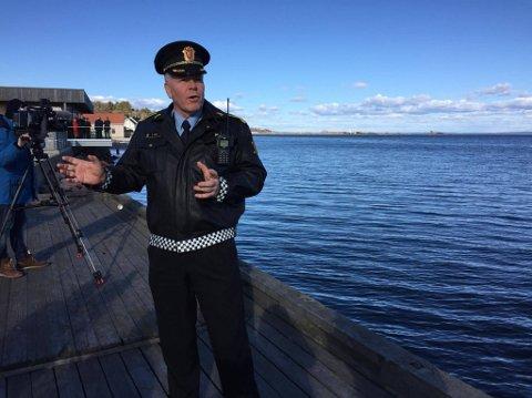 INFORMERER: Frank Gran, leder av politiets ordensseksjon i Tønsberg, informerer pressen lørdag ettermiddag ved Jarlsøbrua. I bakgrunnen ses Vallø, der bomben ble funnet fredag.