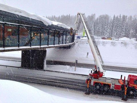 SNØSKAVL: E18 i nordgående felt ble stengt slik at brannmannskapene kunne fjerne en trafikkfarlig snøskavl fra taket over Marché-restauranten.