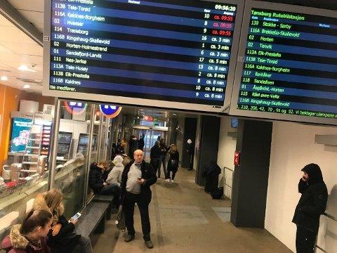 VENTER: Flere passasjerer venter på bussstasjonen i Tønsberg. Svært mange ruter er innstilt tirsdag morgen.