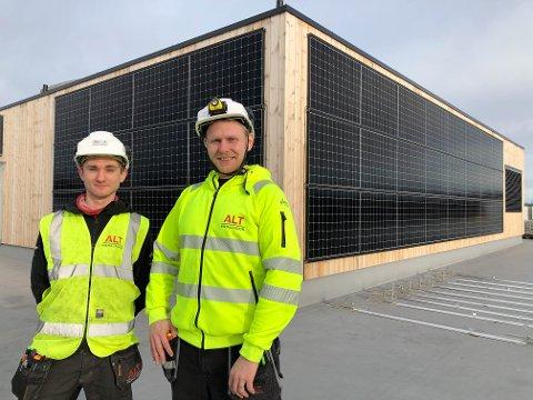 GRØNN FRAMTID: Lærlingene Even Rustan Holmøy (19, til venstre) og Atle Bjelde (33) angrer ikke på valget om å bli elektriker. Her foran solcellepanelene som nå installeres på nye Horten videregående skole. – Det er gøy å være med på det grønne skiftet, sier de to.