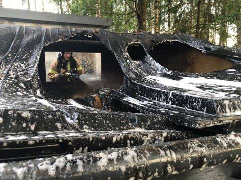 CONTAINERBRANN: Brannmann Alexander Williams slukker brannen i containeren ved steinerskolen i Vestskogen.