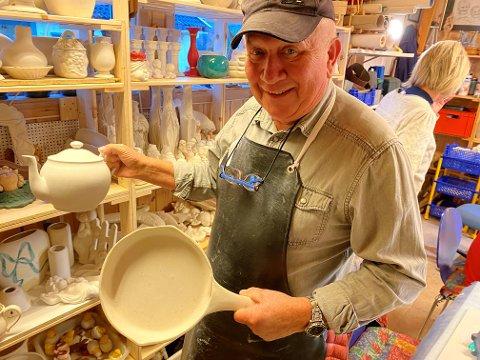 BRUKSGJENSTANDER OG TIL PYNT: Svein Brede Eriksen viser fram noe av produksjonen. Denne kannen og stekepannen skal dekoreres og brennes før de er ferdige.