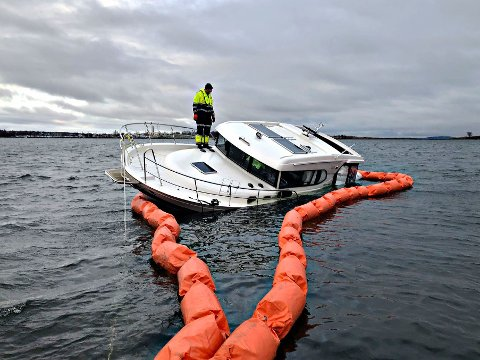 SIKRET: Brannmannskapene har ringet inn båten med en lense som er festet med fire dregger.