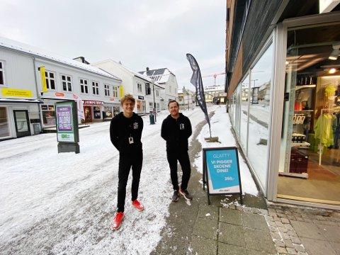 PIGGER: Håvard Fluge Petterson (19) og Ivar Husby (33) ved Löplabbet ser mange skli seg nedover Rådhusgaten fra butikkvinduet. De anbefaler alle å ha et par piggsko eller brodder.