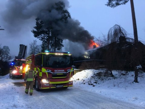 Flammene slo gjennom taket på eneboligen i 15.30-tiden, drøye tre kvarter etter at brannen brøt ut.