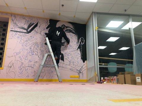 UTFORDRING: Graffitikunstneren fikk i oppdrag å male et motiv ut fra referansen «Bøker stimulerer fantasien».Her er han i startfasen av maleprosjektet.