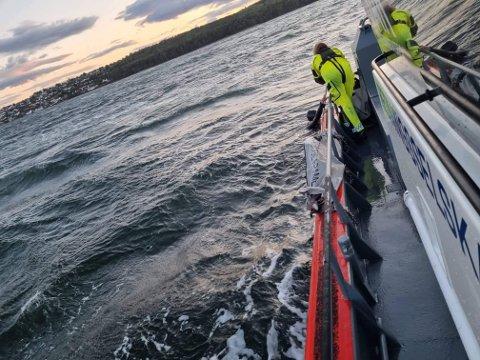 REDDET: Her blir vindsurferen reddet opp i båten til Redningsselskapet.