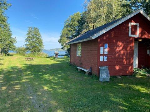 INFO: På den mest populære badeplassen i Akersvannet har Sandefjord kommune hengt opp sitt informasjonsark på denne husveggen, der det blant annet står informasjon om fiskeregler på flere språk. Foto: Atle Møller