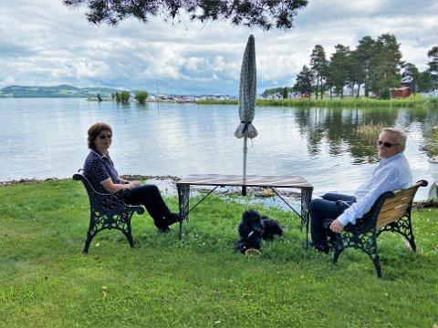 IDYLLISK: Vannkanten har krøpet noen meter opp på plena, men utsikten over Mjøsa, med båthavna og Melkefabrikken like i nærheten, er like fin for Cecilie Schnell-Larsen og Svein Ivar Rakbjørg – enn så lenge.
