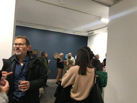 Det var fullt på Kunstnerforbundet i Oslo under utstillingsåpningen torsdag kveld. Sidsel Hanum omgitt av publikummere i bakgrunnen.