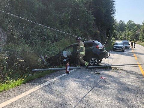Bilen har truffet en lyktestolpe i utforkjøringen, og fått ganske store skader. Her er det mannskaper fra brannvesenet i Tvedestrand som er på stedet. Foto: Karoline Nerdalen Darbo