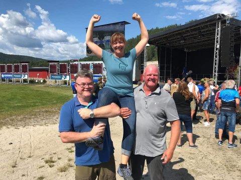 Kirsten Helen Myren løftes opp på «gullstol» av Reidar Saga og Jan Dukene under Landsskytterstevnet på Evje. Privat foto