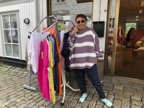 I egen strikk: Anita strikker gensere, gjerne oversized, og i alle mulige fargekombinasjoner. Genserne er noe av det hun selger i butikken sin i gågata i Tvedestrand. Ellers er det mye lin, i alle former og farger, og også klære med trykk, som for eksempel Mikke Mus. Nå håper hun å kunne bli i lokalet i gågata utover. Foto: Siri Fossing