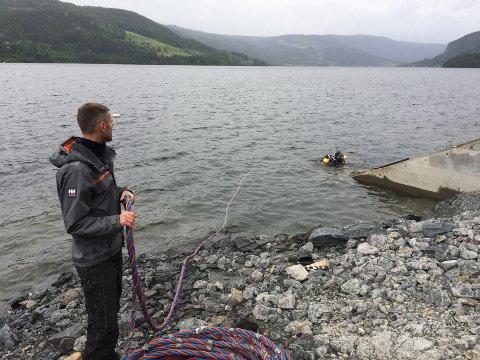 Dykker i Strandefjorden: Dykker Eldar Ailev river forskalingen på vanninntaket, og assisteres av Andreas Arntzen på land.