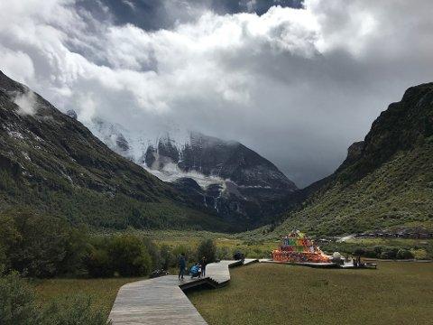 SPEKTAKULÆRT: Innerst i Daocheng Yading Scenic Area, med det hellige fjellet Chenrezig i bakgrunnen. Selve dalbunnen ligger på rundt 4100 meter. Legg merke til gangvegene av tre og det tibetanske bønnetreet. Vi kan også såvidt skimte beitende hester lengst inne.
