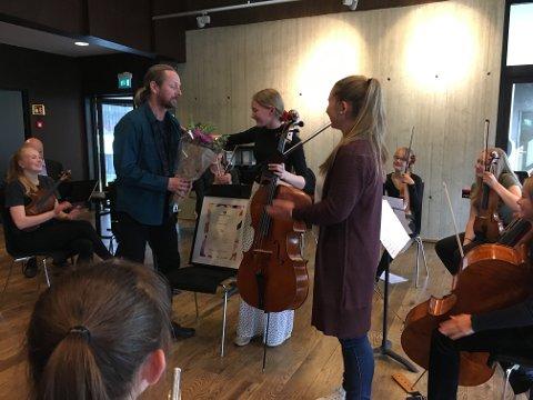Kulturskolerektor Gudbrand Heiene overrekker blomst til Frida som nettopp har mottatt stipendet. Ingebjørg Hegge Bratrud var her representant for Norsk kulturskoleråd og Norsk Tipping.