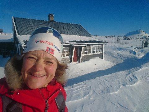 Paradis: Eva Høe ved hytta på Valtjednstølen. Hun er usikker på om det blir hyttepåske i år, til tross for at hun er blant de heldige som har hytte i samme kommune som hun bor i. (Foto: privat)