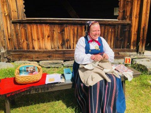 Tekstiler: Kristin Gulbrandsen sitter på en benk utenfor Prestøybygningen, og syr på et korsett.