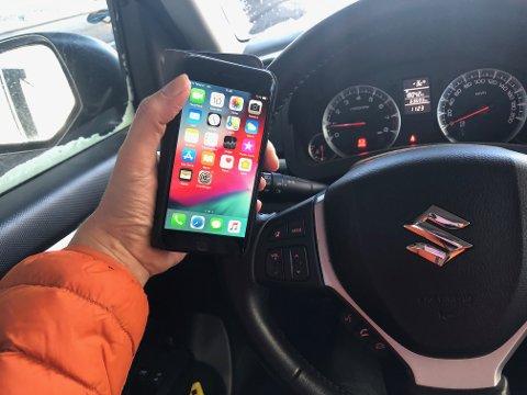 ULOVLIG: Å betjene mobiltelefonen under kjøring er forbudt og straffes primært med bot.