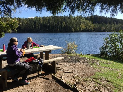 FINT RASTESTED: Turlederne Anne Grete Østernes og Anne Berit Hjermann har testet ut den korteste løypa. Her tar de en rast ved Skredderudtjern på prøveturen, slik det også blir til søndag.