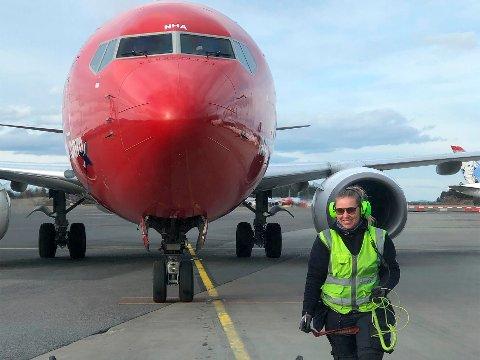 PÅ JOBB FØR KORONA: Ida Hexeberg (24) er lagleder for bakkemannskap på Oslo Lufthavn. I bakgrunnen står et Norwegian-fly snart klar for avgang.