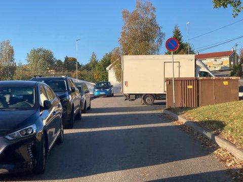 VANSKELIG: Kassebilen til høyre, bak trafoen, står på oppmerket parkeringsplass. Den og andre kassebiler hindrer likevel trafikken i slippsonen til SFO ved Ulverud skole. Parkeringsskiltet til høyre står på feil side i av veien, da det er innkjøring fra motsatt side.