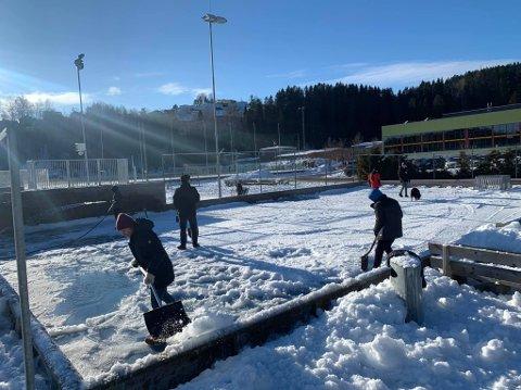 DUGNADSÅND: Lokale barn og voksne fra Li i samarbeid med GIF Storby i full sving med å rydde banen for snø og is.