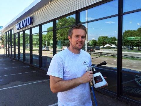 Mathis Haugaasen er klar for å spraye vindusfasaden hos Bil-Service selvvaskende.