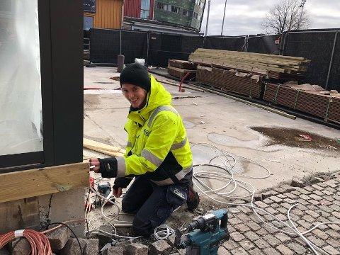 EKSTRA FORSIKTIGE: Lærling Torkil Andreassen (19) fra Nøtterøy  jobbet mandag for at det skal komme lys på det nye tilbygget på utestedet Foynhagen på Brygga. han forteller at de tar spesielle forholdsregler for tiden. – Vi er litt ekstra påpasselige med hygienen og vasker hendene ofte – og spriter litt her og litt der. Det er nok noen som ikke vil ha folk hjem til seg akkurat nå, sier han.