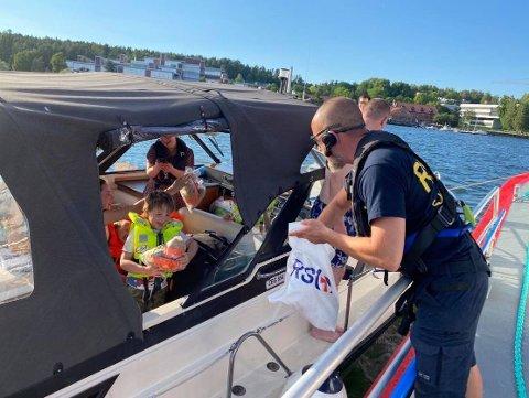 TRØST TIL BARNA: Bertil Spetz deler ut bamser til en famile som gikk på grunne i Oslofjorden. Da ble det god stemning igjen.