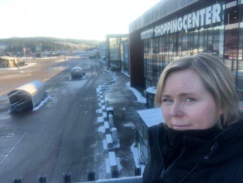 FOLKETOMT: Trine Bjervig viser at det er få biler på parkeringsplassen foran det store kjøpesenteret. At nordmenn uteblir fra grensehandelen får store konsekvenser for blant annet Nordby Shoppingcenter.