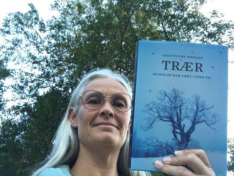 Under tretoppane: Marianne Riste, biblioteksjef ved Vang folkebibliotek, held fram boka ho fell for, «Trettitre norske trær og hva de har vært vitne til».