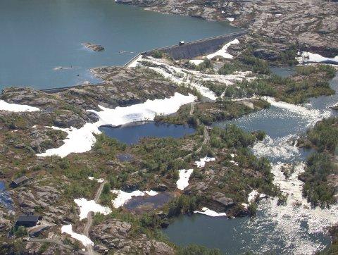 FORSVINNER I VANNMASSENE: Veien som strekker seg fra E10 og innover forbi demningen ved Jernvann har helt forsvunnet i overløpsvannet.