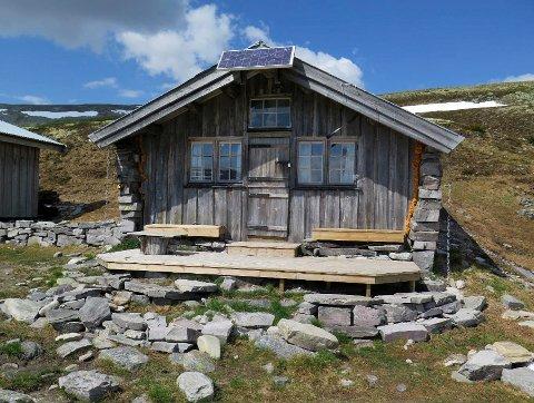 Den verneverdige steinbua i Vulufjell fikk platting i impregnert treverk. Nå må plattingen rives