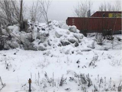 Snøhaugen ved Felleskjøpet kan være til fare for folk, mener Bane Nor. Den gjør det lett å komme over til banesporet.