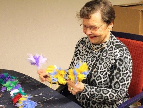 Estel Larsen setter sammen farger og knytter fjær til det som skal bli fastelavnsris.