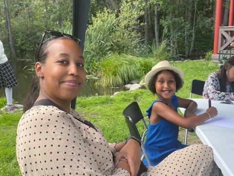 Iman og datteren hygger seg med aktiviteter ved sommerpaviljongen på Holmlia bibliotek.