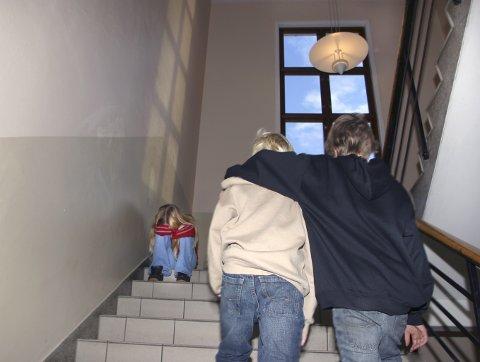 NB! Kun til redaksjonell bruk. En jente sitter sammenkrøpet i en trappeoppgang på skolen. To gutter går opp trappen og forbi henne. Kamerater. Bestevenner. Har blitt ertet, mobbet, trakassert, frosset ut. Venneløs. Trapp. Elever. Elev. Trist. Alene. Ingen venner. Uvenner. Føler seg utenfor. Lei seg. Kranglet. Forlatt. Mishandlet. Skole. Barndom. FOTO: SCANPIX  - - MODEL RELEASED - MODELLKLARERT - -