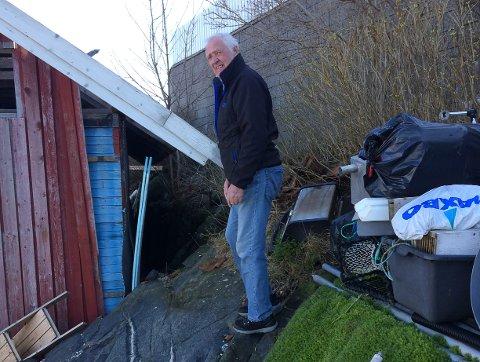 Thore Gunnar Thoresen er mektig lei av å vente på svar fra kommunen. Her står han ved det gamle naustet som han ønsker å erstatte.